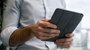 A man looking at audit software on an ipad