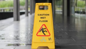 A yellow hazard sign saying caution wet floor with a man slipping over